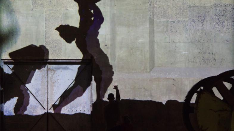 Fotografie eines Schattenspiels gegen eine große Mauerwand.