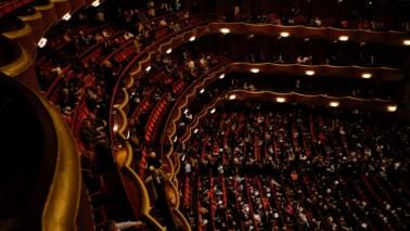 Fotografie eines Opernsaals aus der Vogelperspektive. Die Stühle sind mit rotem Stoff überzogen.