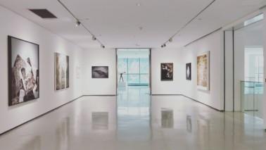 Foto eines hellen Ausstellungsraumes. Zu sehen ist ein Ganz, links und rechts an der Wand hängen verschiedene Bilder.