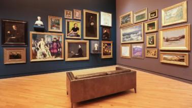 Foto eines Ausstellungsraumes, Im Raum steht eine braune Bank. Eine Wand ist mit blauer Farbe gestrichen, die andere mit einer hellbraunen Farbe. An den Wänden hängen mehrere Bilder.