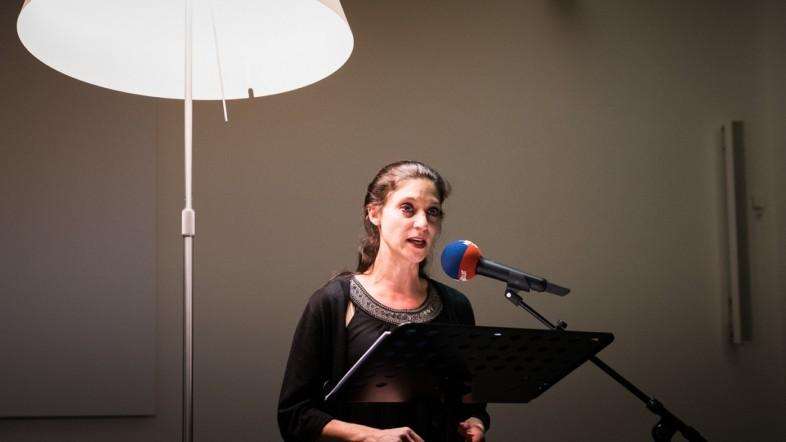 Eine Frau steht auf einer Bühne vor einem Podest. Sie ist schwarz gekleidet und spricht in ein Mikrofon.