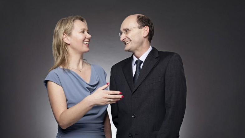 Eine Frau in einem blauen Kleid und ein Mann in einem schwarzen Anzug stehen vor einer dunklen Leinwand. Die beiden schauen sich an und lachen.