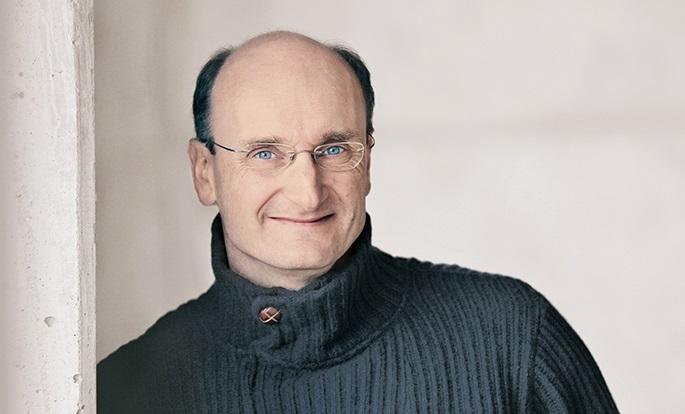 Der Dirigent Andrew Manze steht vor einer hellen Mauer. Er trägt einen Pullover und eine Brille.