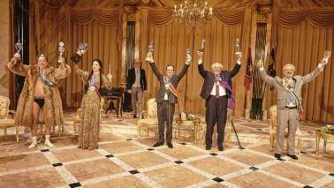 Mehrere Personen stehen auf der Bühne, schick gekleidet, lachen und halten Pokale in die Luft.