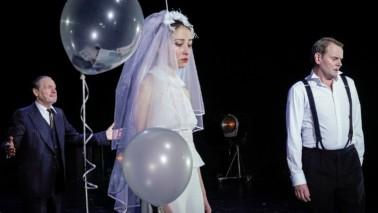 Auf einer Bühne steht eine Frau im Brautkleid, die weint. Links neben ihr sind durchsichtige Ballons. Der Hintergrund ist schwarz und zwei Männer sind zu sehen.