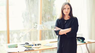 Foto von Line Hoven in einem hellen Raum. Sie steht vor einem Fenster, trägt ein Kleid und verschränkt die Arme.