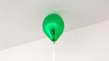 Foto eines grünen Ballons, der an der Decke eines hellen Raumes schwebt.