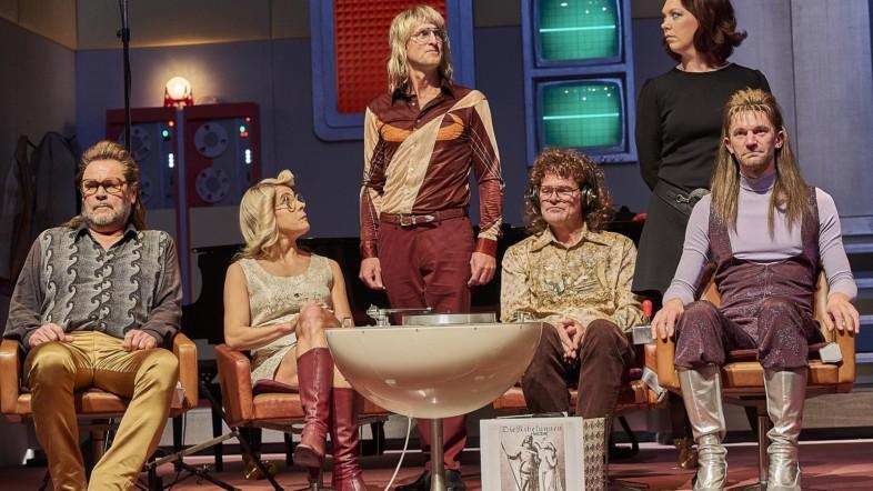 Mehrere Personen sitzen auf Stühlen auf der Bühne und schauen Richtung Publikum.