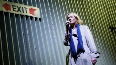 Eine Frau steht vor einer Wand, auf der ein Exit Schild befestigt ist. Die Frau hat blonde Haare, trägt einen Mantel und einen Schal um den Hals. Ihr Haar ist blond und sie hält ein Mikrofon in der rechten Hand.
