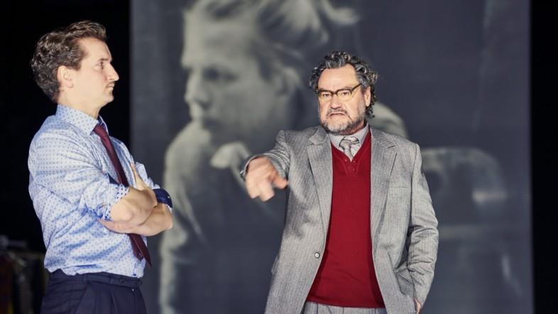 Zwei Männer stehen auf der Bühne. Der Mann auf der linken Seite trägt ein hellblaues Hemd und verschränk die Arme. Der Mann auf der rechten Seite zeigt mit dem Zeigefinder auf den Mann auf der linken Seite der Bühne. Er trägt einen hellgrauen Anzug mit einem roten Oberteil und schaut verärgert aus.