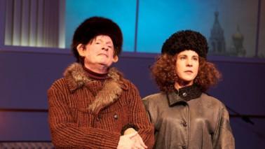 Ein Mann und eine Frau stehen auf der Bühne. Sie tragen dicke Jacken und schwarze Pelzhüte. Die Frau hakt sich mit dem Arm bei dem Mann ein.