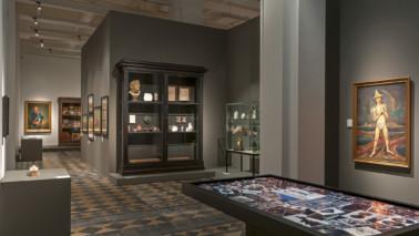 """Foto eines Ausstellungsraumes der Ausstellung """"Raum der Geschichte"""" im Erdgeschoss des Herzog Anton Ulrich-Museums. Der Raum ist dunkel gestaltet."""