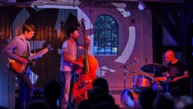 Foto aus Sicht des Publikums auf eine Bühne, aus der verschiedene Künstler stehen. Es ist dunkel und auf die Bühnen scheinen verschiedene Lichter. Die Künstler spielen alle ein Instrument.