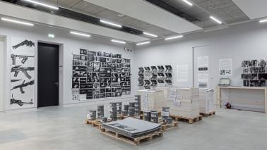 Innenansicht des Kunsthauses Göttingen. Zu sehen in ein hellgrauer Raum. An der Wand hängen mehrere schwarz/weiß Bilder und verschiedene Gegenstände und Materialien stehen auf dem Boden im Raum verteilt.