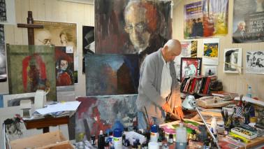 Ein älterer Mann steht in einem Raum voller Gemälde.