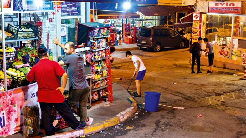 Foto einer Straße bei Nacht. Auf der linken Seite ist ein beleuchteter Kiosk zu sehen. Auf der Straße laufen ein paar Männer. Einer davon säubert die Straße.