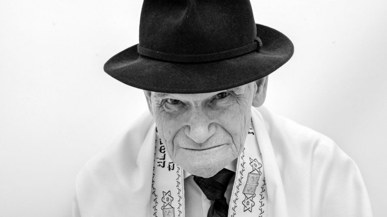 Schwarz weiß Portrait von einem alten Mann der einen Hut trägt.