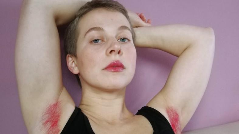 Eine Frau mit kurzen Haaren sitzt auf einer Couch und verschränkt die Arme über dem Kopf. Sie trägt ein schwarzes Top und ihre Achselhaare sind pink gefärbt.