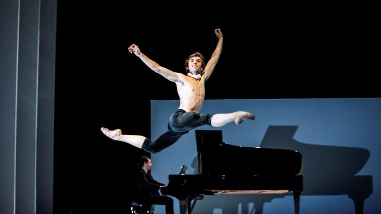 Ein Tänzer springt vor einem Klavier elegant durch die Luft.