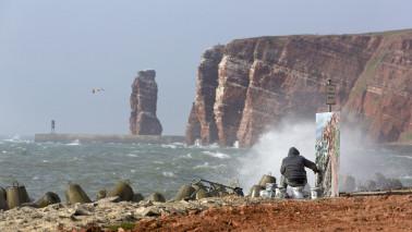 Ein Mann sitzt am Meer und malt auf einer Leinwand. Im Hintergrund sind große Felsen zu sehen.