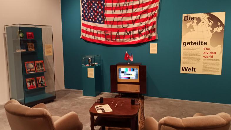 """Bild eines nachgebauten Wohnzimmers, an der Wand eine große amerikanische Flagge auf die jemand """"Hände weg von Mittelamerika"""" geschrieben hat. Reil der Ausstellung Auf den Spuren des Kalten Krieges im Freilichtmuseum Molfsee."""
