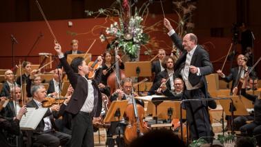 Ein Junge und ein Mann stehen auf einer Bühne und musizieren. Im Hintergrund ist ein Orchester zu sehen.