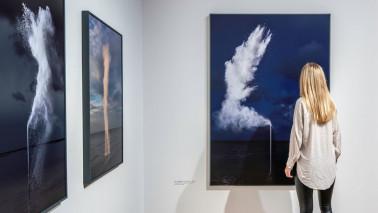 Eine Frau steht in der Ausstellung Sjoerd Knibbeler In Elements vor mehrere Fotografien.