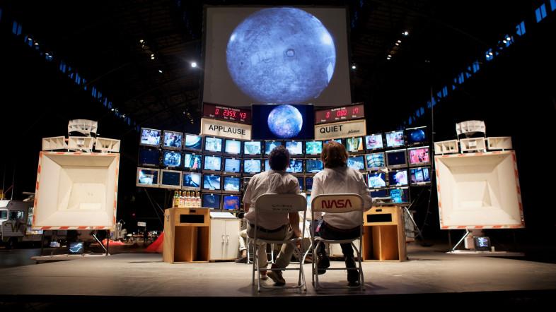 """Zwei Personen sitzen in einem nachgebauten Mission Control Center als Teil der Ausstellung """"Tom Sachs: Space Program: Rare Earths"""""""